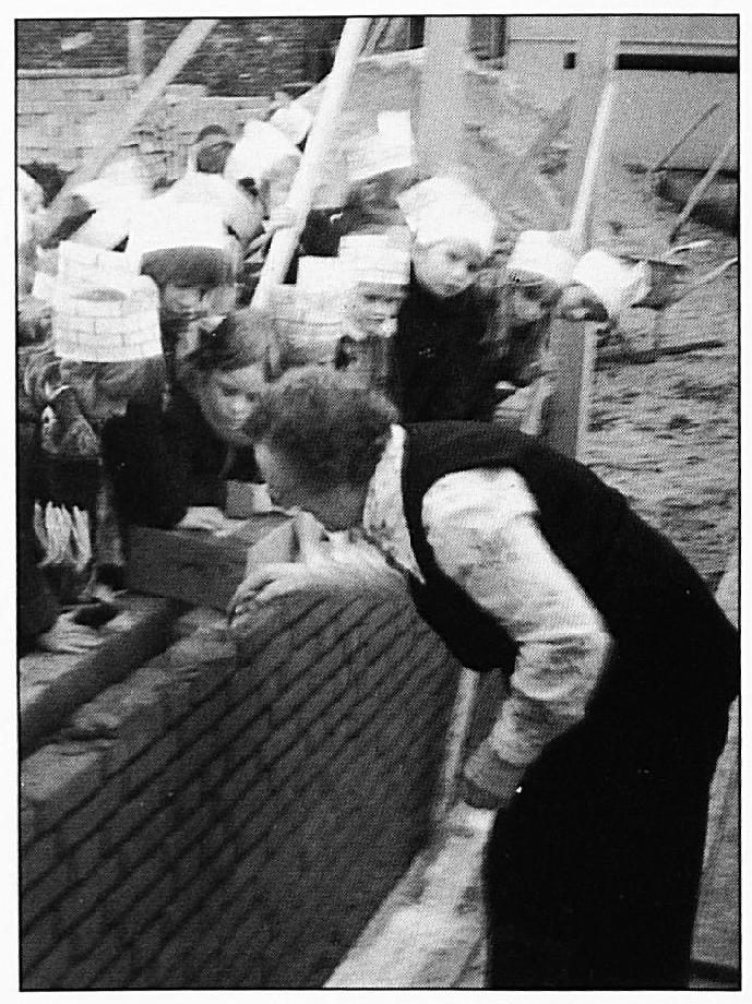 """Zuster Bertranda legt """"de eerste"""" steen voor de nieuwe kleuterschool aan de Lakenstraat."""