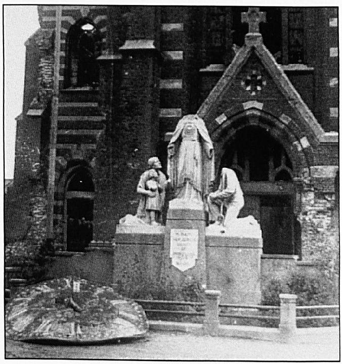 Het beschadigde H. Hartbeeld met op de achtergrond de vernielde kerk en op de voorgrond de verwrongen wijzerplaat van de kerk toren-uurwerk.