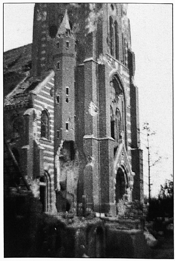 De zwaar gehavende kerktoren met links de schamele resten van het huis van Sengers.