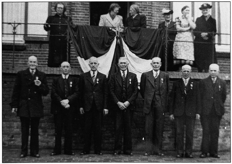 """Op het bordes v.l.n.r. de dames: Martens, Hofman, Debast, Van Zuidam, Van Vliet en Van Zuidam. Op de voorgrond v.l.n.r.: Marinus van Zuidam, Wim van Zuidam, Dirk Hofman, Christinus Hofman, Has Hofman, Debast en Martens. De foto werd gemaakt voor het huis van """"ovenbaas"""" Van Maanen, t.g.v. het feit dat de heren 40 jaar werkzaam waren op de Wamelse steenoven. Burgemeester Ditters had juist daarvoor de ridderorden uitgereikt."""