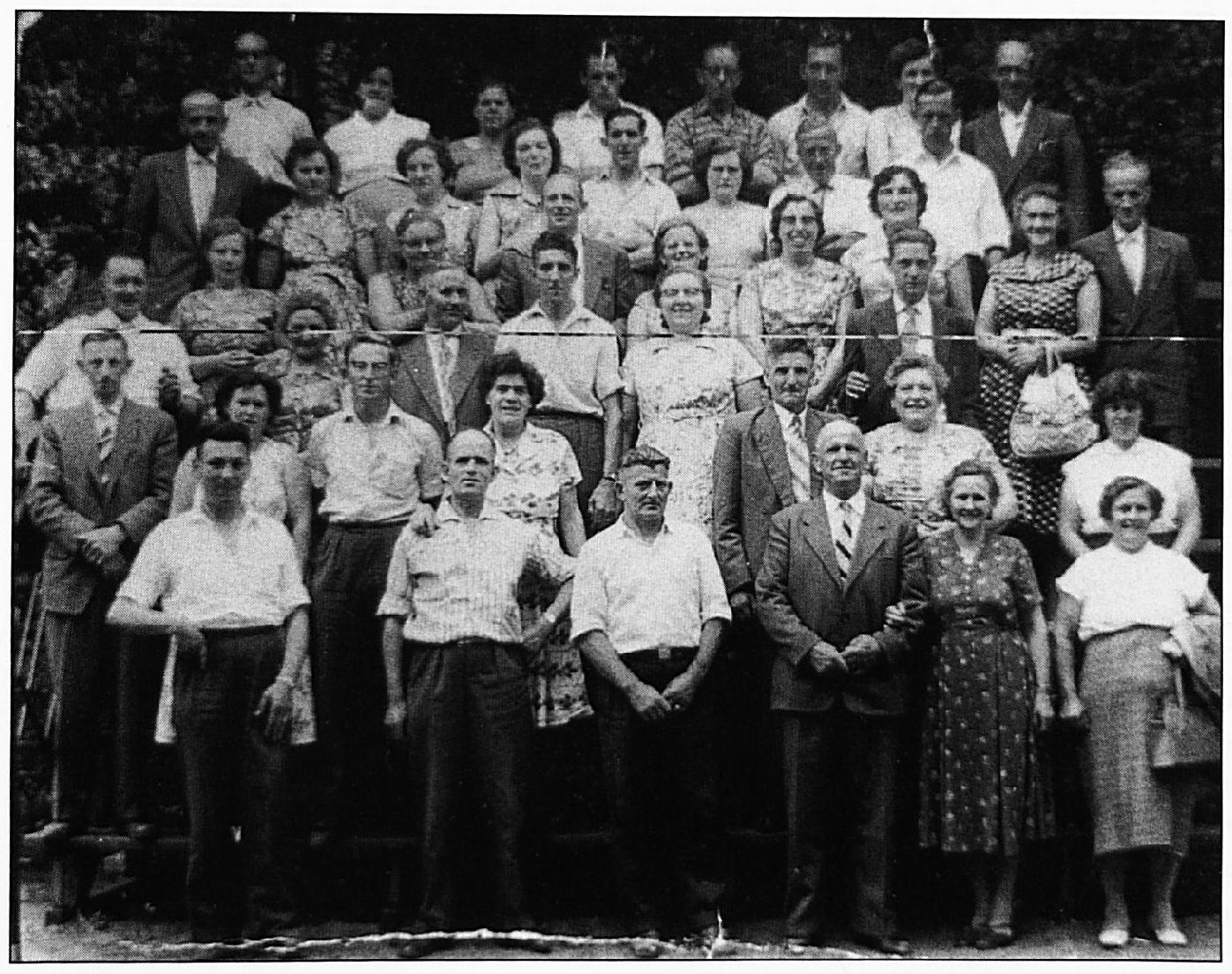 """Eind 1955 werd de reisvereniging """"Ons Vermaak"""" opgericht, dit was een onderdeel van de vakbeweging metaal, St. Eloy. Achterste rij v.l.n.r.: Cor van Rossum, Mevr. Van Rossum, Mevr. Janssen, Herman Janssen, Arno Janssen, Jacob Janssen, Mevr. Scheeren, Gert Scheeren. Tweede rij van achteren v.l.n.r.: Jo van Kessel, Mevr. Van Kessel, Mej. Janssen, Mevr. Zondag, Lambert Zondag, Mevr. Van Gelder, Lambert van Gelder, Piet van Lent. Derde en vierde rij van achteren, v.l.n.r.: Mevr. Visee, Mevr. Peters, Gradus Gerritsen, Mevr. Van Lent, Wim Walraven, Mevr. Walraven, Jan Peters, Jan Zondag, Mevr. Zondag, Mevr. Gerritsen, Mevr. Koolhout, Piet van Zwam, Mevr. Van Dodewaard, Stef van Dodewaard. Zesde rij van achteren, v.l.n.r.: Frans Zondag, Adri Wolvers, de chauffeur van de bus, Arno v.d. Locht, Mevr. v.d. Locht, Mevr. Nuy."""