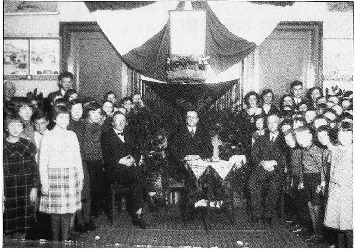 In de openbare school aan de Dorpsstraat werd een feestelijke ontvangst gehouden voor de nieuw benoemde burgemeester Ditters. De burgemeester zit in het midden. Geheel links achteraan meester Kersten.