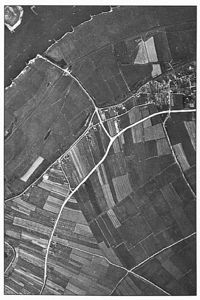 """Op deze luchtfoto uit 1954 is de Van Heemstraweg te zien toen deze werd aangelegd. Rechts van de (v.a. de Waalbandijk) eveneens nieuw aangelegde Veerweg is een """"wit"""" terrein te zien. Hier stond de tijdelijke betonfabriek waar men de specie voor het wegdek maakte. Wat meer naar links is goed te zien dat de Van Heemstraweg daar het tracé van de Lage Weg volgt. Men kan aan de versmalling iets verder op precies zien hoe ver men op dat moment gevorderd is met de aanleg."""
