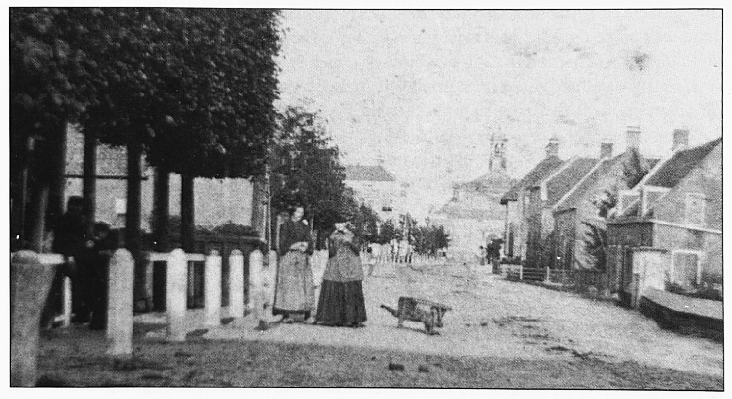 """Dit is waarschijnlijk de oudste foto van Wamel. Aan het eind van de Dorpsstraat ziet men met het torentje de """"Koepelkerk"""" die in 1828 gebouwd werd. De foto moet gemaakt zijn vóór het najaar van 1878, want toen werd begonnen met de bouw van de nieuwe kerk."""