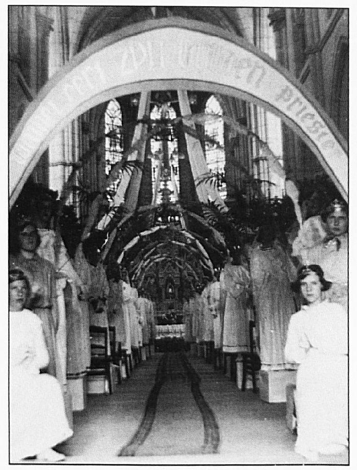 Een indrukwekkende erehaag van bruidjes met sierlijk versierde bogen staat klaar om pastoor Heurkens te ontvangen.