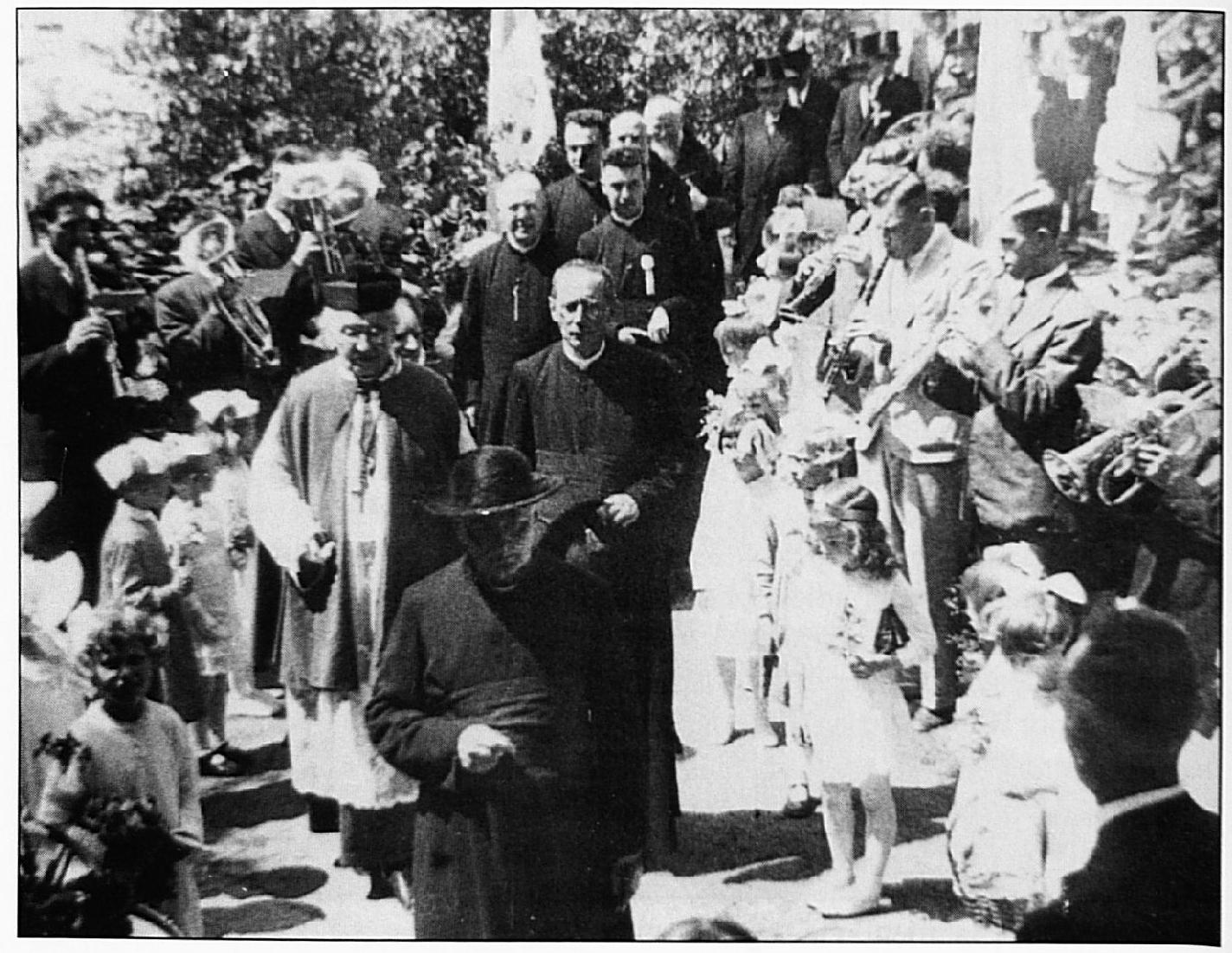 De jubilaris wordt met muziek van de Harmonie ontvangen in zijn pastorietuin.