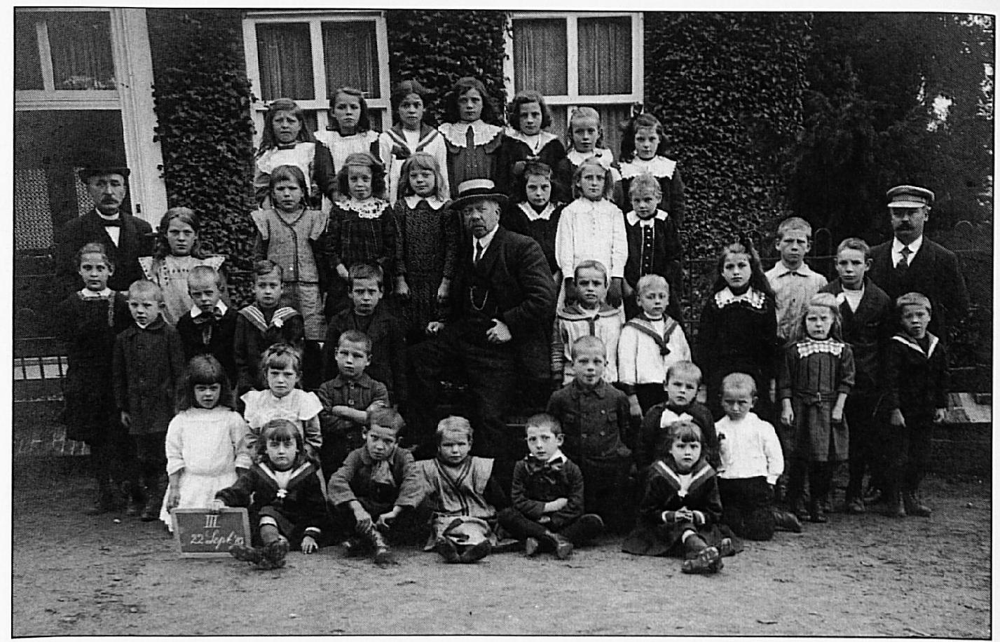 Deze derde schoolfoto van 22 sept. 1919 toont op de achterste rij v.l.n.r.: Anna Laponder, Jaan Peters, Filomeen Maas, Marie Melis, Riek Melis, Gon van Lent, Toos Nijs. Tweede rij van achteren: Meester Vincent, ..... , ..... , Anneke van Lent, Truus Melis(?), Grada Nijs, ..... , ..... Derde rij van achteren: ..... , Thé Melis, Johan van Lent, Harry Maas, .. ... , Meester Otten, Adri Peters, Jo Meijer, Nel Peters, Johan Melis, Cees Peters. Meester Van Oijen, ervoor staan Nellie Peters en Albert van Oijen. Vierde rij van achteren: ..... , ..... , Johan(?) van Kessel, Harry \1elis, Chris Peters, Ernst van Oort(?). Voorste rij: Cato Visser, Toon van Lith, ..... , Marinus Nijs, Riek Visser.