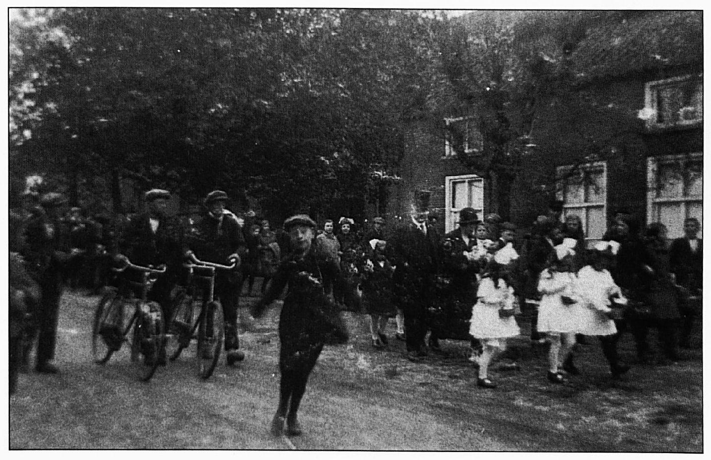 In het midden -met hoge hoed- loopt meester Van Oijen en zijn vrouw. Het betreft de viering van zijn zilveren jubileum, waarbij hij omringd werd door bruidjes. kinderen, genodigden en belangstellenden.