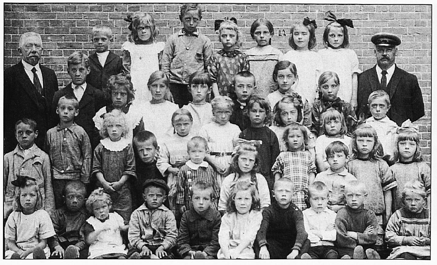 Deze schoolfoto stamt uit 1924/ 1925. In tegenstelling tot de voorgaande foto's beginnen we nu v.l.n.r. op de voorste rij: Aaltje Oosterholt, Johan Vermeulen, Tonnie Janssen, Toon van Oort, Wim Vermeulen, (?)Vincent, Jan van Teeffelen, Gerard Vincent, Kees van Verseveld, Neeltje van Verseveld. Tweede rij: Jo van Zwam, Jan van Oorsouw, Joke Janssen, Thé Vermeulen, Gerard de Vaan, Nolda Vincent, Doortje van Deursen, Johan van Os, Nelly van Oijen, Corry van Oijen. Tussenrij, beginnend met het meisje dat boven Toon van Oort half tussen Thé Vermeulen en Gerard de Vaan in staat: Katrien van Oort, Marie van Oort , Tonnie van Deursen, An Vermeulen, Riek Visser, Even Verwoert. Tweede rij van boven: Meester Otten, Niek van Oorsouw, Marietje Janssen, Lies de Vaan, Anneke Vermeulen, Cato Visser. Achterste rij: Sam Janssen, Leen Janssen, Giel Janssen, Nolda van Oorsouw, Jaan Verkerk, Fien Vem1eulen, Nel Visser, Meester Van Oijen.