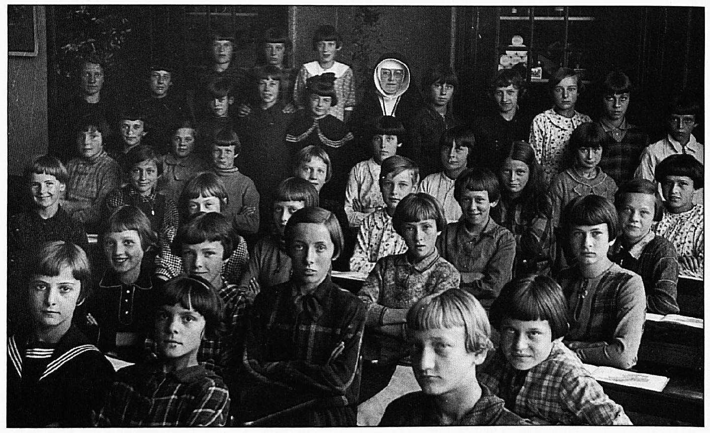 Twee foto's uit 1937, op de eerste foto ziet U van rechts voor naar achter zittend: Annie Meyer, Cis v.d. Hurk, Mar. van Echteld, Jo van Deursen, Pieta van Teeffelen. Tweede rij: Ietje Zondag, Jo Reijnders, Jo Vermeulen, Jo Martens, Nel v.d. Heuvel. Derde rij: Lena Pompen, Corrie van Rijn, Anneke Bouman, Hermien van Elk, Riek van Kessel. Vierde rij: Gonnie van Rossum, Truus Bouman, Sj. van Rossum, Annie Duifhuis. Vijfde rij: A. v.d . Heuvel, Bets van Kessel, Thea van Bergen, Annie Pardoel. Zesde rij : Cilia Sengers, Sjaan Beck. Staande v.l.n.r.: Juffrouw Truus de Rouw, Riek Post, lneke Nuy, Nelly Bouman, Gradeke Gerritsen, Zr. Ludgardi s, Nel Gerritsen, Tonnie Giesbers, Riek van Elk, Annie Gerritsen, tussen de laatste twee in ervóór Elia Putters en aan het eind A. van Zwam. Links boven geheel achteraan staande: An Post, Luus van Echteld en Benha Gerritsen.